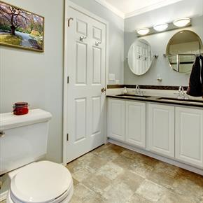 Modern bath with checked beige floor round mirrors and double sinks
