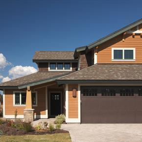 Wooden siding & shingle home w/ brown garage door & gable & angled asphalt roof