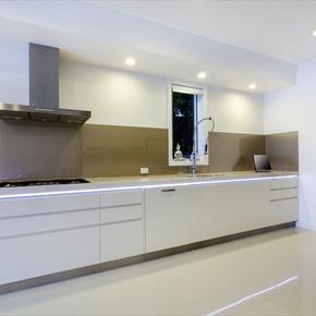 Flat brushed aluminum range hood featured in white modern kitchen