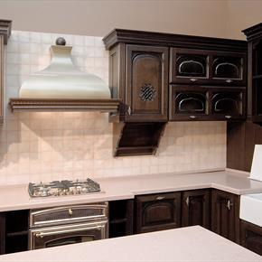 Custom nickel range hood surrounded by dark walnut celtic design cabinets