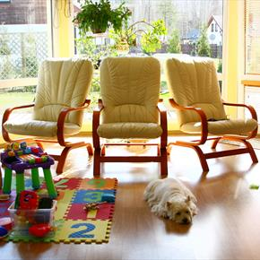 Sunroom and play space with wood grain look floor, chairs and toys