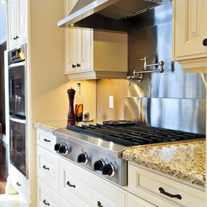 Classic stainless wall mounted range hood in kitchen with off white cabinets