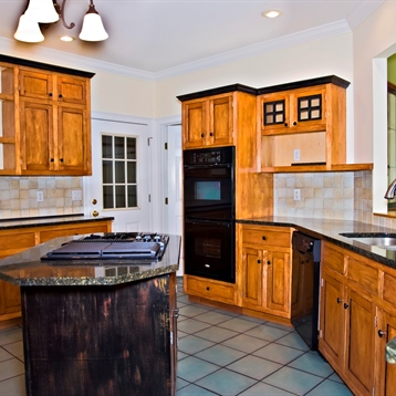 Rustic kitchen cabinets with granite countertops and neutral tile backsplash