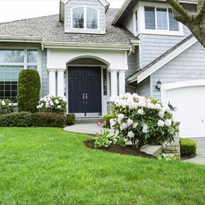 Gray shingle, 2-story house with white trim and black front door