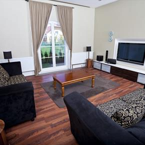 Modern living room with swirl-patterned sofas and wall-mounted television